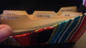 "The striped pouch contains tiny index card-sized files, labeled ""Hotel,"" ""Flight,"" ""Ground,"" and ""Air"""