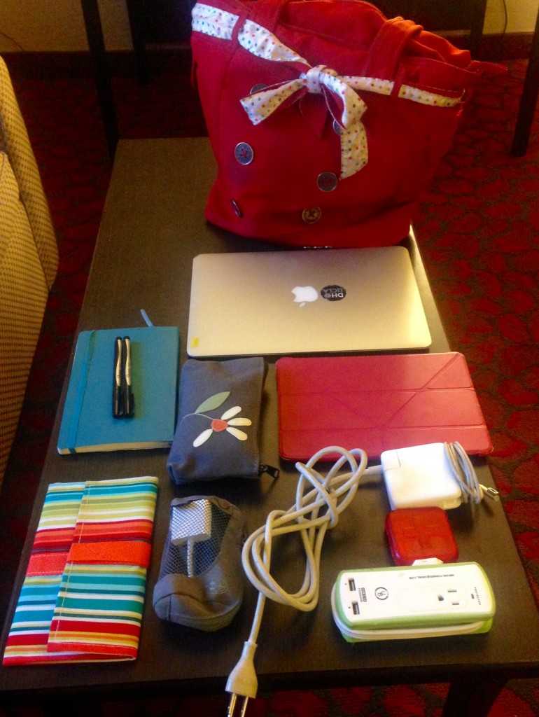 A red purse sits in the backyard. In front are a laptop, notebag, pens, two small gray zippered pouches, a power adapter, a power strap, a pill case, and a striped pouch.