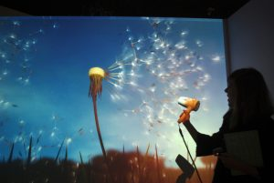Woman holds a hair dryer in front of a screen depicting a dandelion. The dandelion's seeds appear to be blowing away by the hair dryer.