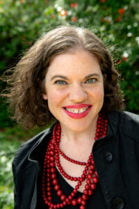 Headshot of a smiling white woman with dark hair, wearing a black jacket and shirt and a red necklace
