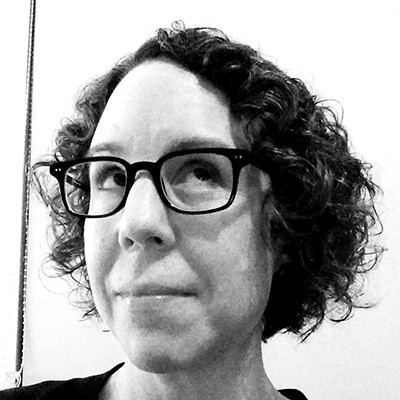 Black-and-white photo of a white woman with dark curly hair and glasses, looking up and to the side.