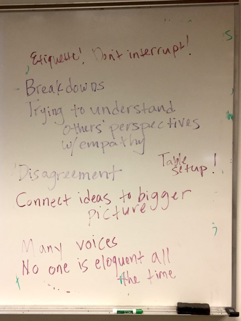 "Whiteboard text reads, ""Etiquette! Don't interrupt,"" ""Breakdowns,"" ""Trying to understand others' perspectives w/empathy,"" ""Table setup!"" ""Disagreement"" ""Connect ideas to bigger picture"" ""Many voices"" and ""No one is eloquent all the time."""