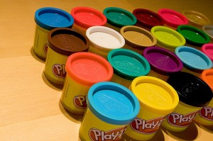 Many plastic tubs of Play-Doh, each a different color.