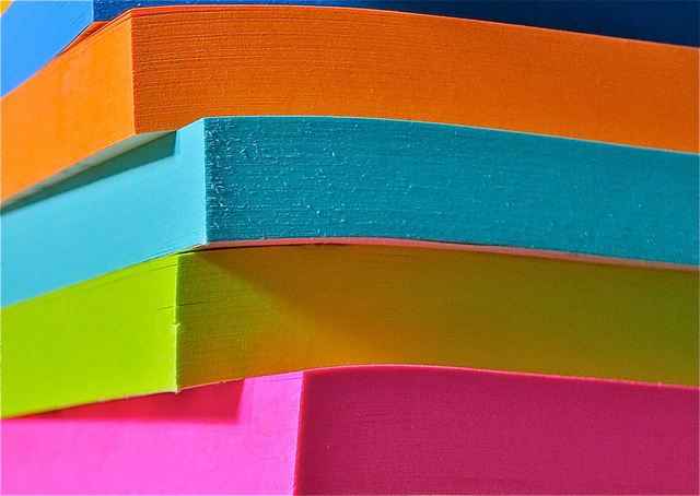 a stack of orange, blue, yellow, and pink post-it-notes